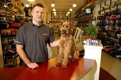 Über uns - Carsten Neugebauer steht hinter dem Verkaufstresen. Auf dem Tresen sitzt sein junger Hund Theo. Neugebauer streichelt seinen Hund, während er freundlich in die Kamera guckt.