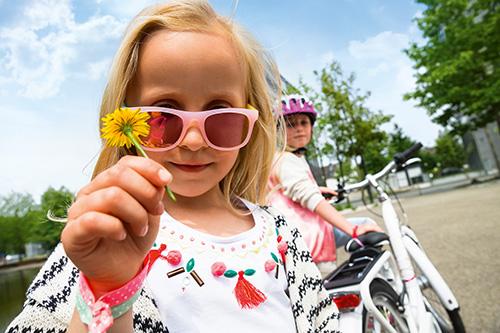 Puky - lächendes Mädchenmit Blume in der Hand
