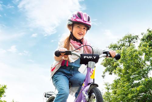 Puky - strahlendes Mädchen mit Puky Helm fährt mit einem Puky Fahrrad einen Blumenabhang hinunter.