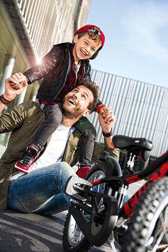 Puky - ein Vater trägt seinen Sohn huckepack, wobei das Puky Fahrzeug im Vordergrund das passende Farbdesign zur Mode des Jungen hat.